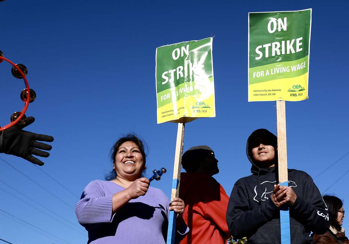 Isabel Burgos and her son, Adrian Burgos, 12, a 7th grade student at Melrose Leadership Academy, participate in the Oakland Teachers Strike outside the school in Oakland, Calif., on Thursday, February 21, 2019.