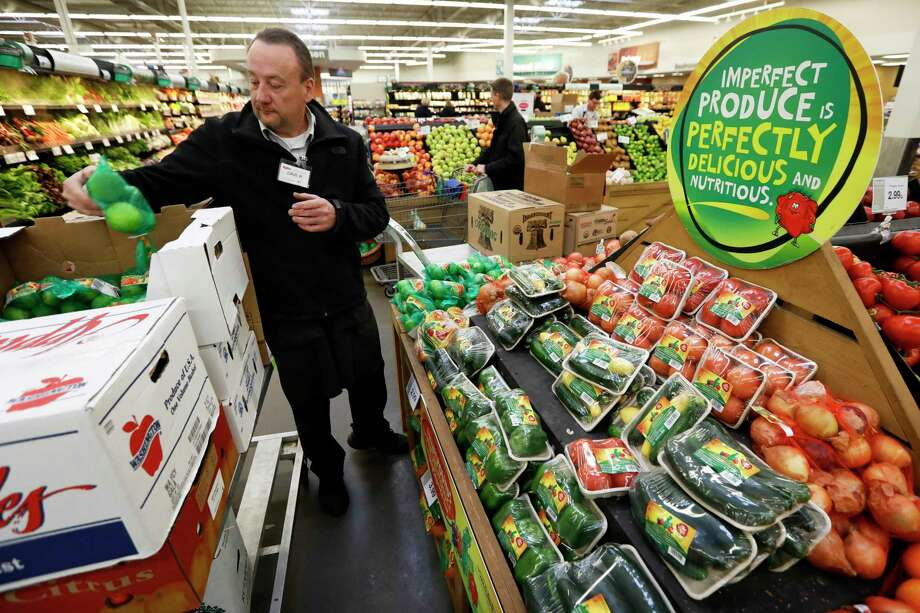 In this Friday, Jan. 18, 2019, photo, assistant produce manager Dave Ruble stocks the imperfect produce section at the Hy-Vee grocery store in Urbandale, Iowa. After enjoying a brief spotlight in supermarket produce sections, blemished fruits and vegetables may already be getting tossed back in the trash. (AP Photo/Charlie Neibergall) Photo: Charlie Neibergall / Copyright 2019 The Associated Press. All rights reserved