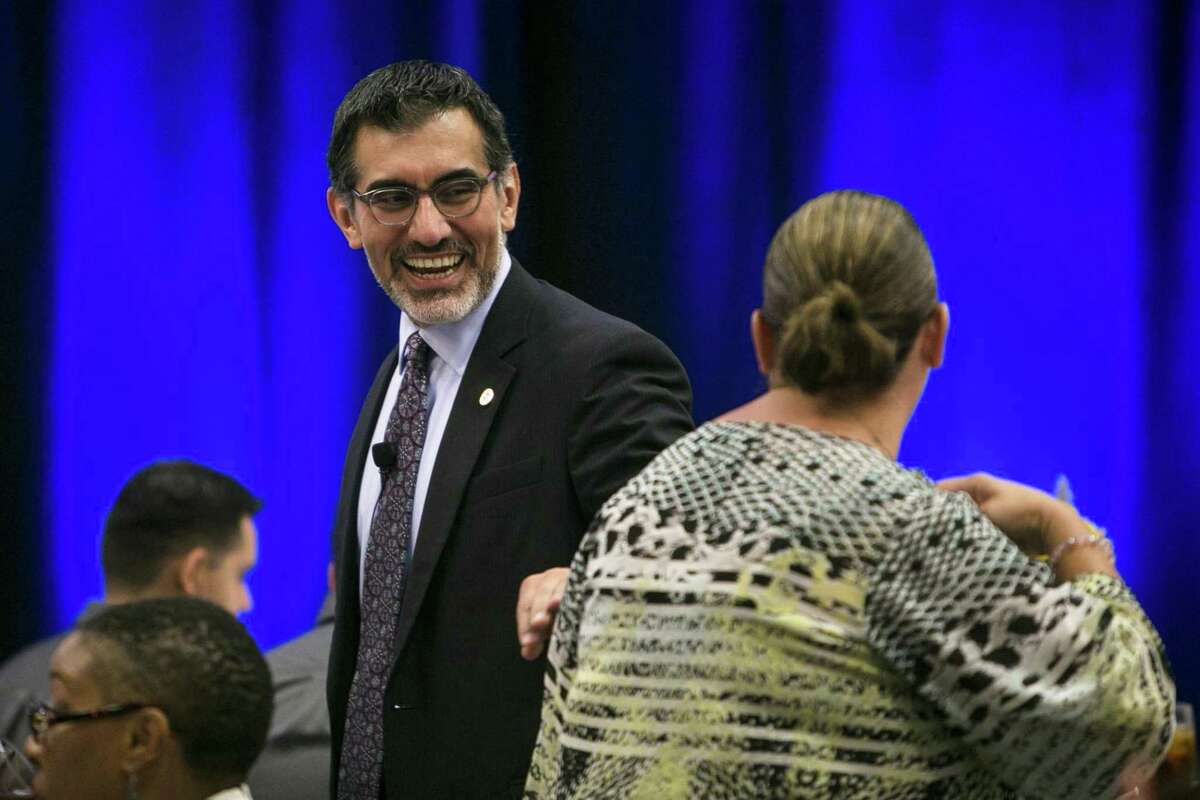 """Newly appointed chancellor of the Alamo Colleges Mike Flores shares a laugh with an attendee before speaking at the Hispanic Chamber luncheon held at Embassy Suites at Brooks Oct. 10. The recent announcement of the """"Alamo Promise"""" could be a game-changer for many Bexar County students."""