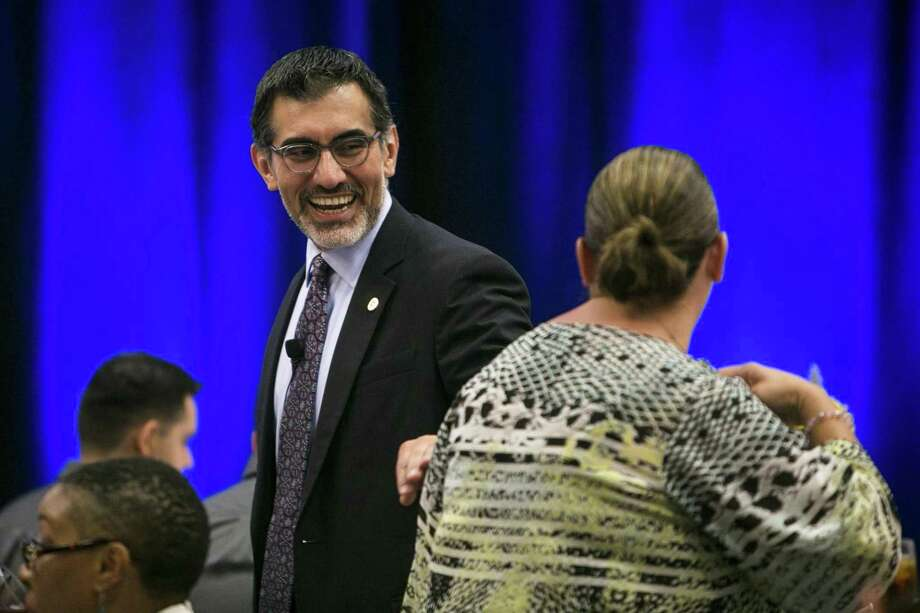 "Newly appointed chancellor of the Alamo Colleges Mike Flores shares a laugh with an attendee before speaking at the Hispanic Chamber luncheon held at Embassy Suites at Brooks Oct. 10. The recent announcement of the ""Alamo Promise"" could be a game-changer for many Bexar County students. Photo: Josie Norris /San Antonio Express-News / © San Antonio Express-News"