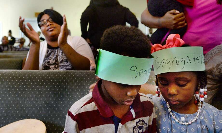Z'aiden Warnell (left) and Ja'Leigh Tims, wearing the headbands they made in pre-service Bible study learning about Black history, occupy themselves with a game while congregants join in hymns of praise during Sunday morning services at Mount Zion Missionary Baptist Church in Orange, Feb. 19, 2017. Black History Month is an opportune time to learn of cultures besides one's own and break away from racism as a nation. Photo: Kim Brent /Beaumont Enterprise