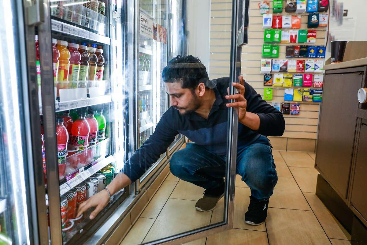 7-11 employee Rajan Bhatti checks if he needs to re-stock the soda refrigerators at the 7-11 on Mission Street in San Francisco, California, on Monday, Feb. 18, 2019.
