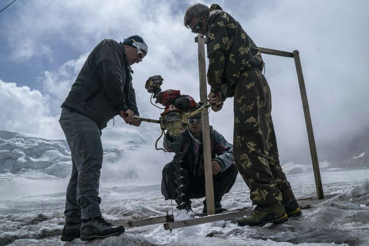 Researchers work with an array of measuring stakes planted in holes in the ice on Tuyuksu glacier in Kazakhstan in August, 2018. The glacier is melting rapidly. What isn't melting fast enough is the resistance to doing something about climate change.