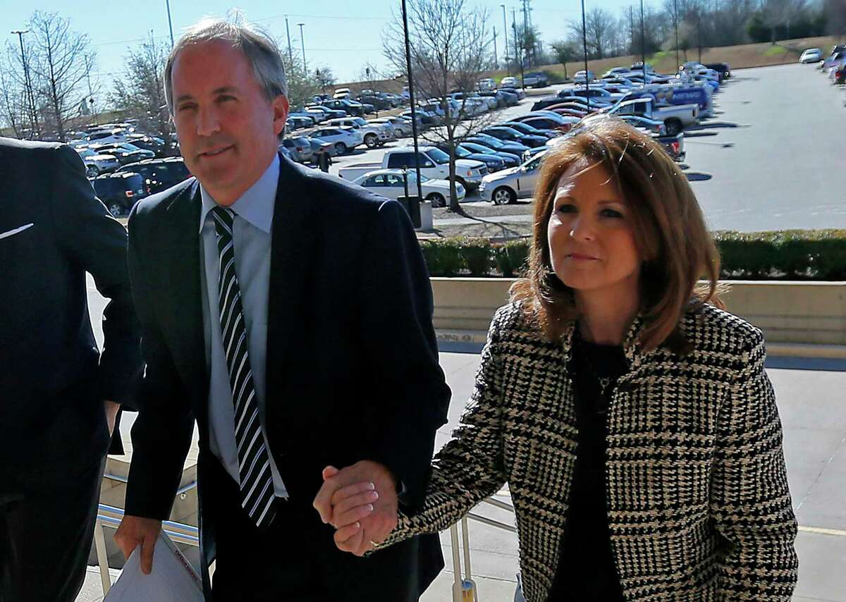 FILE - In this Feb. 16, 2017, file photo, Texas Attorney General Ken Paxton, left, arrives at the Collin County Courthouse with his wife Angela in McKinney, Texas. The wife of Texas Attorney General says a bill she filed that would change state securities law