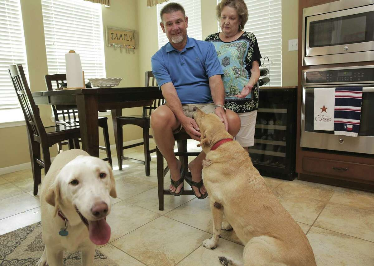 Richard and Maxine Kelley in their home with their labs, Hunter, left, and Hondo on Friday, July 20, 2018 in Tomball. Richard fell and hit head on corner of his kitchen island in January, a couple days later he walked into a freestanding ER where a doctor saw him for a few minutes, provided no treatment except a nurse giving him some steri-strips. The visit was coded as mid-level severity level and the bill was $1000 which insurance paid $300, leaving them with a $800 out of pocket cost. ( Elizabeth Conley / Houston Chronicle )