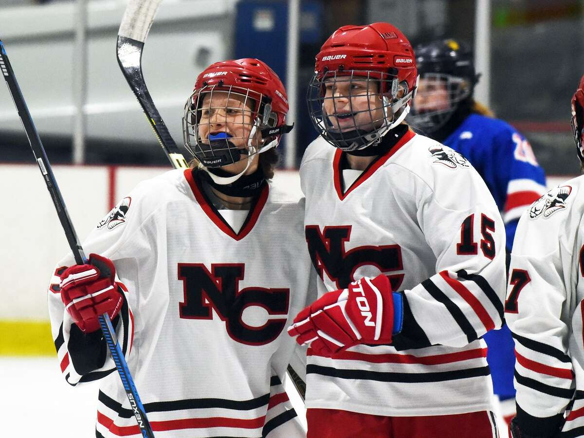 New Canaan freshmen Jade Low (left) and Caitlin Tully (15) celebrate Lowe's second-period goal during the FCIAC girls hockey semifinals at the Darien Ice House on Thursday, Feb. 21. - Dave Stewart/Hearst Connecticut Media photo