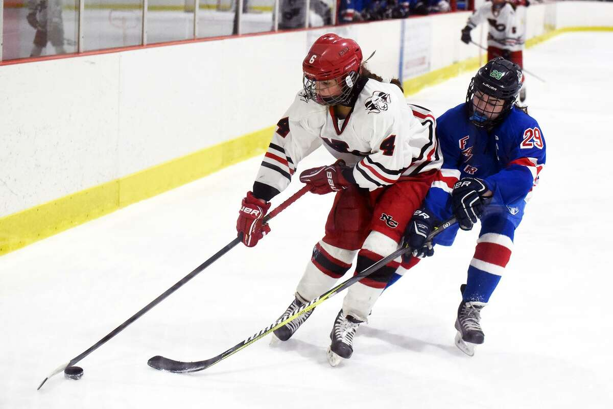 New Canaan's Kaleigh Harden (4) controls the puck while Fairfield's Jessica Pitaniello (29) defends during the FCIAC girls ice hockey semifinals at the Darien Ice House on Thursday, Feb. 21. - Dave Stewart/Hearst Connecticut Media photo