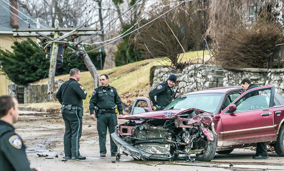Alton police officers search a vehicle that fled a traffic stop and crashed into a power pole at the intersection of Liberty and Union streets Thursday evening. The driver was taken into custody. Photo: Nathan Woodside | The Telegraph