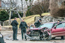 Alton police officers search a vehicle that fled a traffic stop and crashed into a power pole at the intersection of Liberty and Union streets Thursday evening. The driver was taken into custody.