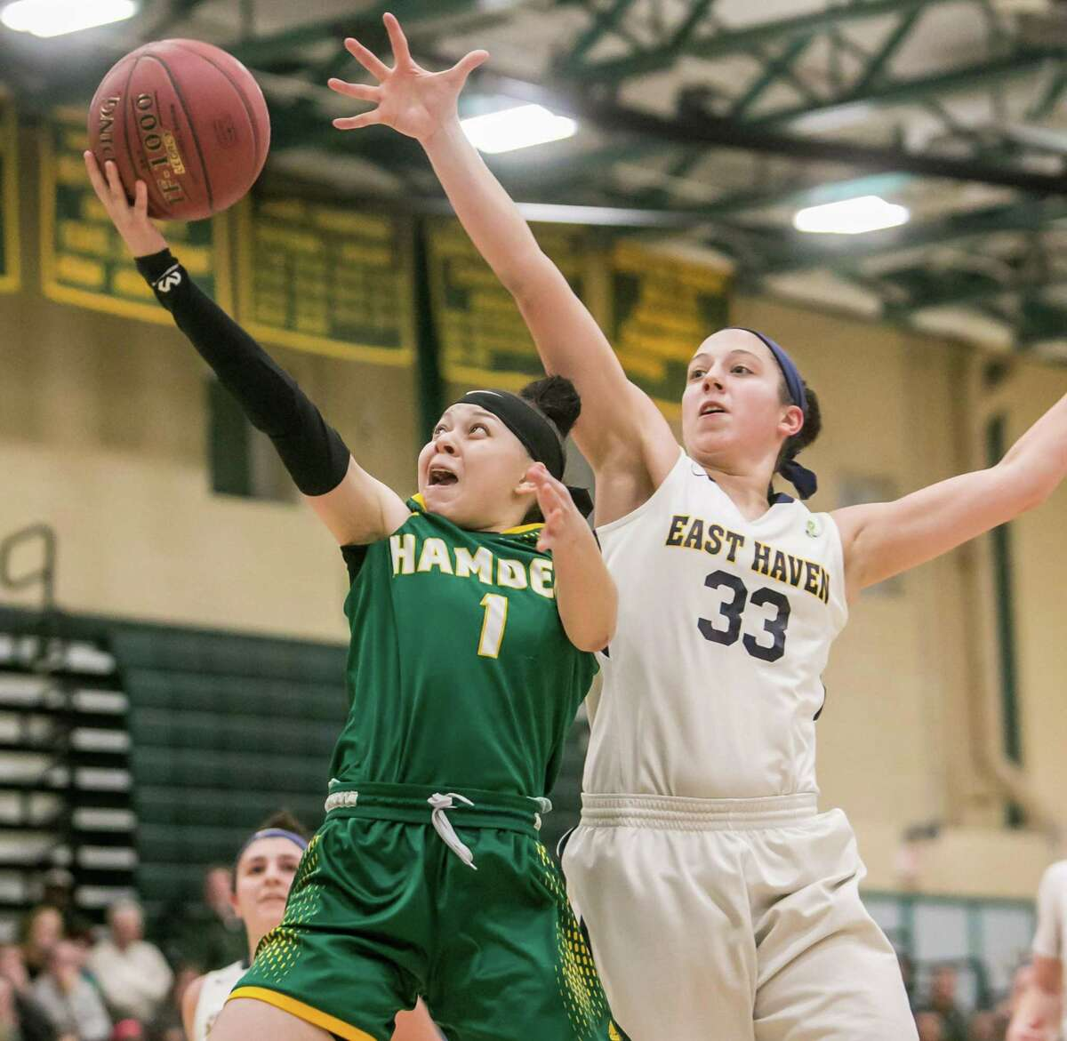 Hamden's Asya Brandon goes in for a layup past East Haven defender Taylor Salato during the SCC championship game on Thursday.
