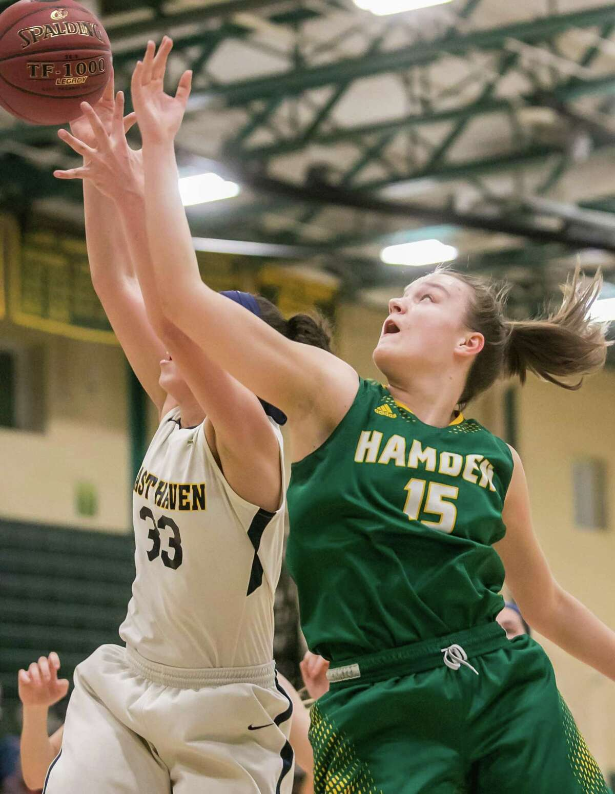 Hamden's Rebecca Oberman-Levine goes up for a rebound with East Haven's Taylor Salato during the SCC championship game on Thursday.