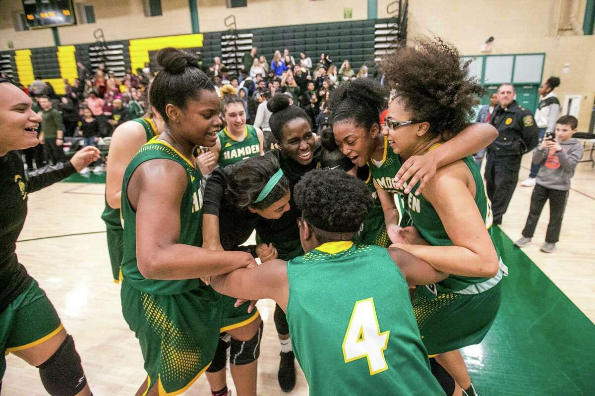 Members of the Hamden girls basketball celebrate after winning the SCC championship on Thursday.