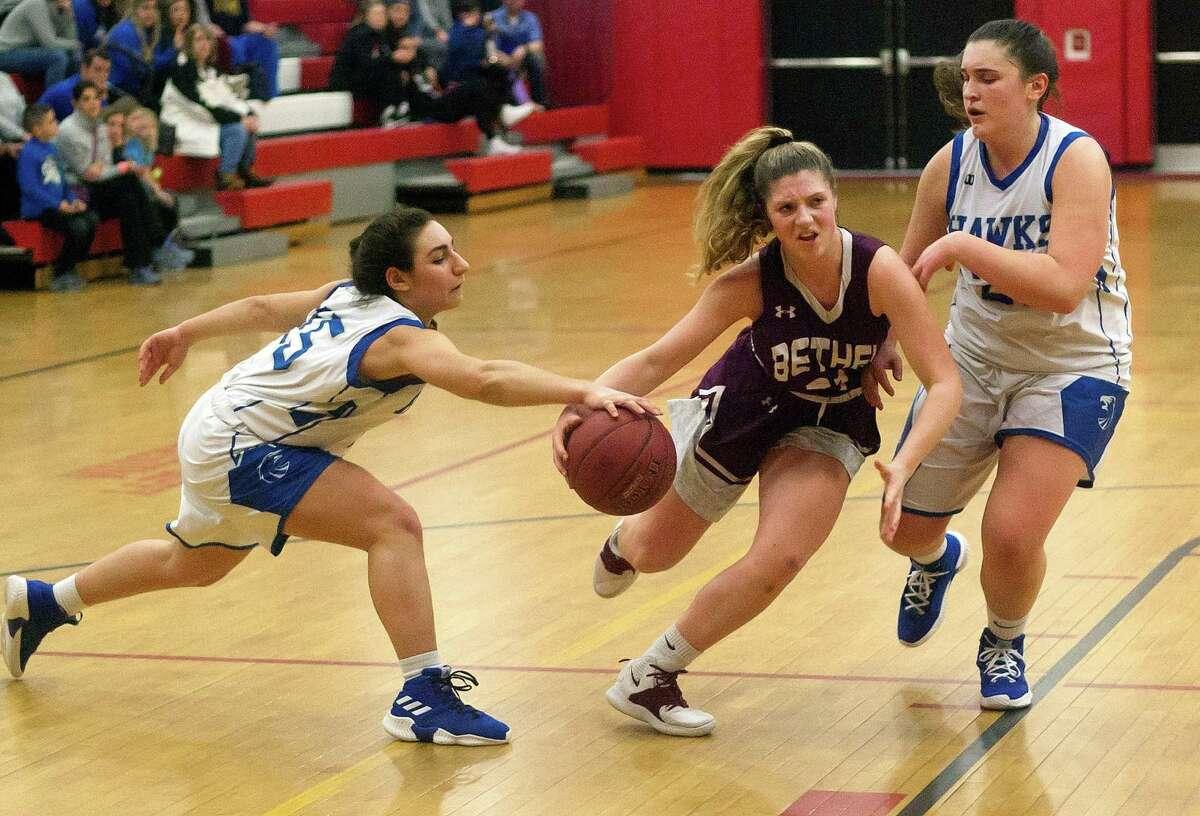 Newtown's Jacquelyn Matthews (15) reaches in to knock away the ball from Bethel's Ruby Ackerman (21) during SWC girls basketball championship game action in Southbury, Conn., on Thursday Feb. 21, 2019.