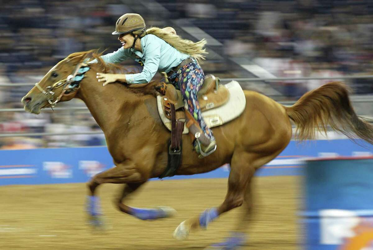 The Woodlands Township special, pilot bus route to The Houston Livestock and Rodeo Show this year is now a bit cheaper after township officials reduced the price to $13 a round trip at their Feb. 21 meeting. Here, Tanner Learmont gets bucked off a bull into a wall during the Wild Card Bull Riding competition at the Houston Livestock Show and Rodeo at NRG Stadium, in 2018.Fallon Taylor is all smiles as she rides to first place in barrel racing during the 2018 Super Series V Round 3 of the Rodeo Houston on Tuesday, March 13, 2018, in Houston.