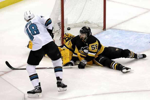 San Jose Sharks' Tomas Hertl (48) shoots past Pittsburgh Penguins goaltender Casey DeSmith (1) for a goal, his first of the NHL hockey game, with Penguins' Kris Letang (58) also defending in the first period in Pittsburgh, Thursday, Feb. 21, 2019. (AP Photo/Gene J. Puskar)