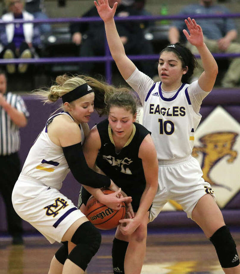 CM's Jenna Christeson (left) ties up Springfield SHG's Sophie Lowis, who was caught in a double team with CM's Kourtland Tyus (10) in the fourth quarter Thursday night at the Taylorville Class 3A Sectional. Photo: Greg Shashack / The Telegraph