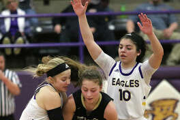 CM's Jenna Christeson (left) ties up Springfield SHG's Sophie Lowis, who was caught in a double team with CM's Kourtland Tyus (10) in the fourth quarter Thursday night at the Taylorville Class 3A Sectional.