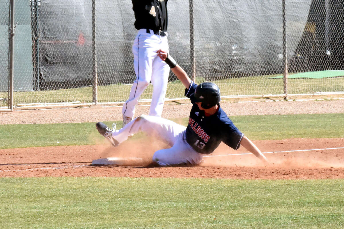 Plainview Bulldogs No. 2 hitter Kole Mayberry slides safely into third base, beating the throw to Big Spring's Jason Miramontes during the season-opening 9-0 victory on Thursday morning in Plainview.