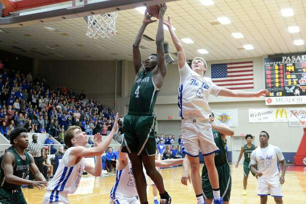 Chris Felix (4) of Hightower drives to the basket past Max Armer (C) (4) of Barbers Hill during the second half of a Class 5A, Region III area-round basketball playoff game between the Hightower Hurricanes and the Barbers Hill Eagles on Thursday, February 21, 2019 at the Phillips Field House, Pasadena, TX.