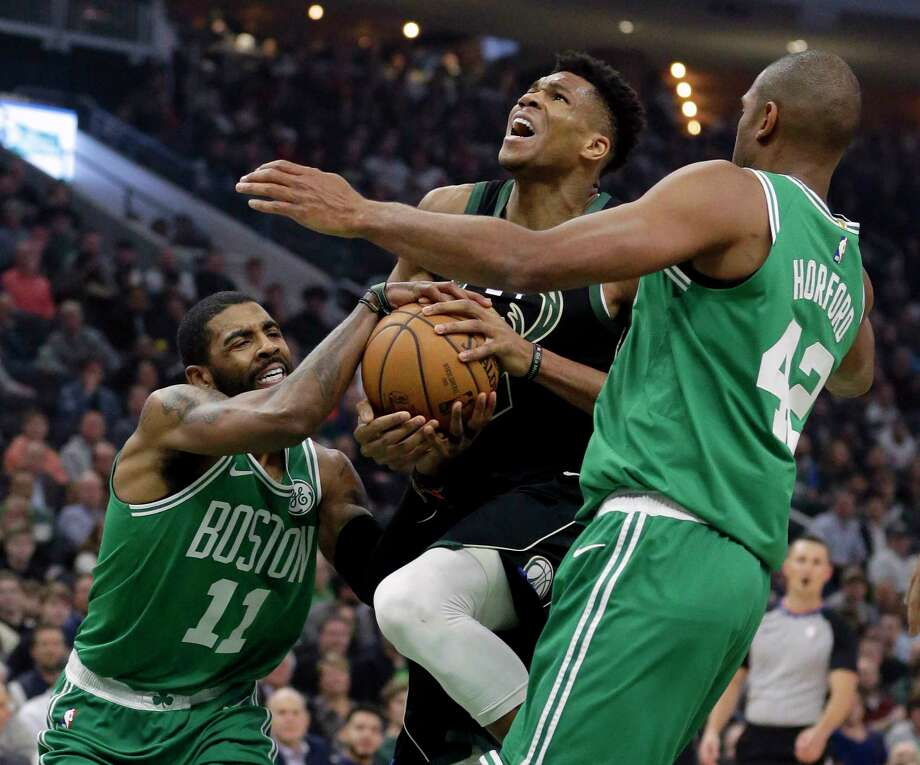 Boston Celtics' Kyrie Irving (11) forces a jump ball against Milwaukee Bucks' Giannis Antetokounmpo, center, during the first half of an NBA basketball game Thursday, Feb. 21, 2019, in Milwaukee. (AP Photo/Aaron Gash) Photo: Aaron Gash / Copyright 2019 The Associated Press. All rights reserved.