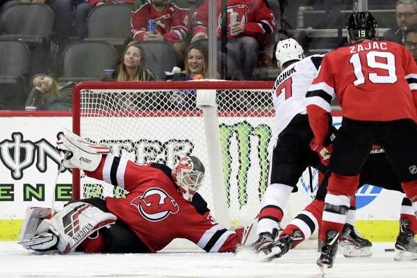 New Jersey Devils goaltender Cory Schneider, left, falls to the ice while reaching to defend against Ottawa Senators left wing Brady Tkachuk (7) during the second period of an NHL hockey game, Thursday, Feb. 21, 2019, in Newark, N.J. (AP Photo/Julio Cortez)