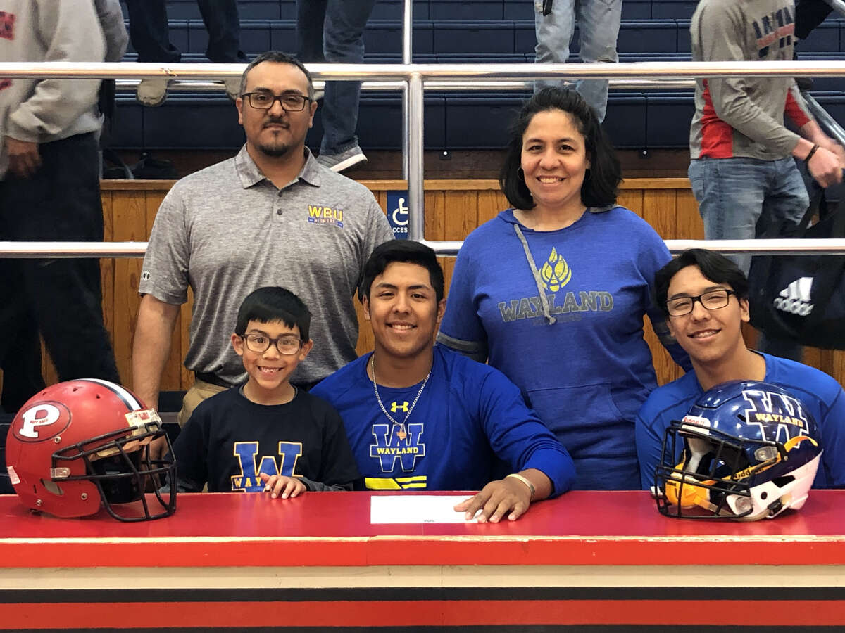 Andrew Villa (center) is surrounded by his family as the Plainview Bulldog signs his national letter of intent to play football at Wayland Baptist University on Wednesday at Bulldogs Gym in Plainview.