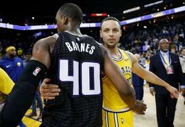 Golden State Warriors' Stephen Curry greets Sacramento Kings' Harrison Barnes after Warriors' 125-123 win in NBA game at Oracle Arena in Oakland, Calif., on Thursday, February 21, 2019.