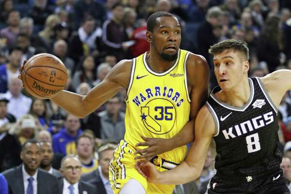 Golden State Warriors' Kevin Durant drives against Sacramento Kings' Bogdan Bogdanovic in 1st quarter during NBA game at Oracle Arena in Oakland, Calif., on Thursday, February 21, 2019.