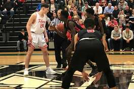 Hargrave's Kade Harvey (24) and Furr's Stephan Morris (32)prepare for the tip-off at the beginning of an Area playoff game on Feb. 21 at Kingwood Park High School.