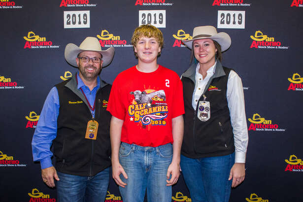 Landry Miller (center) stands with volunteers of the San Antonio Rodeo Association's Calf Scramble Committee after catching a calf.