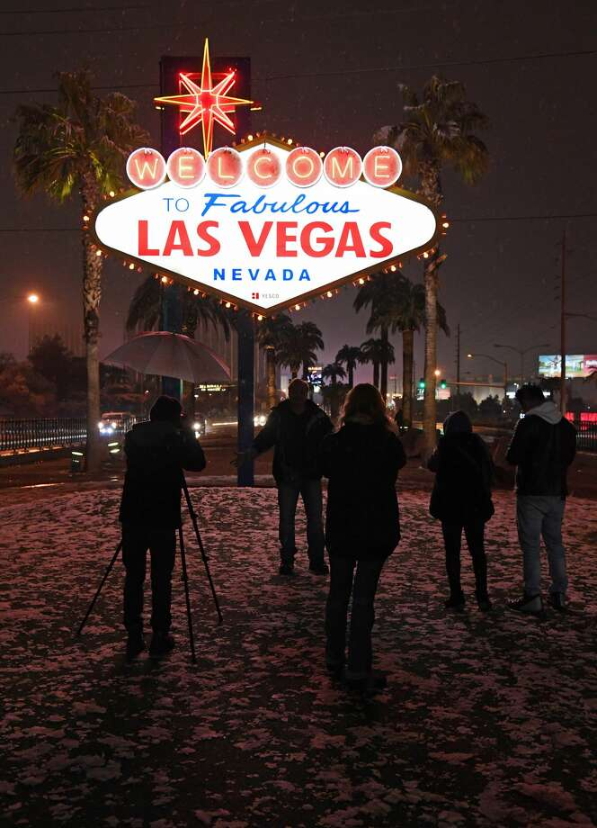 LAS VEGAS, NEVADA - FEBRUARY 20  A photographer uses an umbrella to protect his camera from snow as he and other visitors take photos at the Welcome to Fabulous Las Vegas sign during a winter storm on February 20, 2019 in Las Vegas, Nevada. The National Weather Service in Las Vegas issued a winter weather advisory for the area overnight.  (Photo by Ethan Miller/Getty Images) Photo: Ethan Miller/Getty Images
