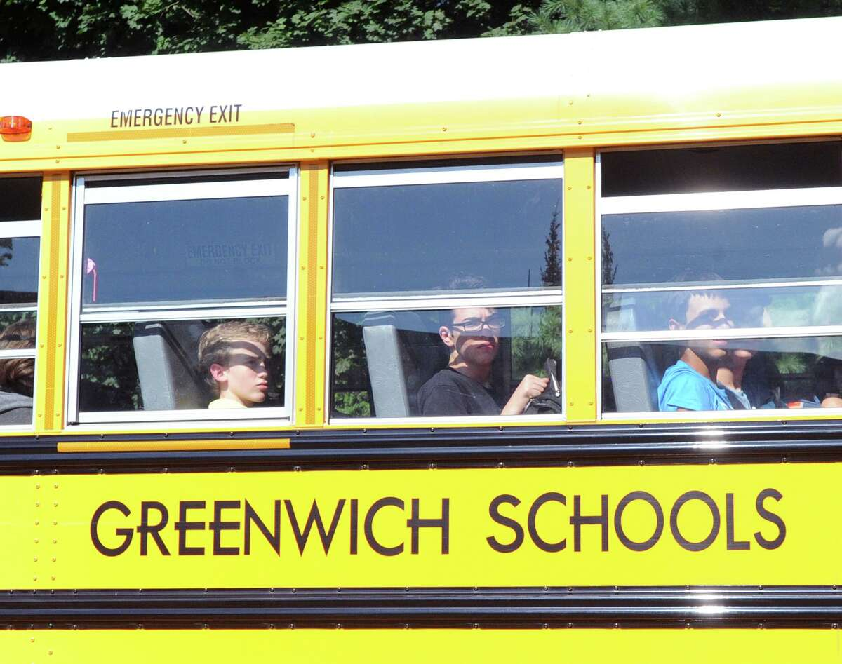 GHS students ride a school bus on Hillside Road in front of Greenwich High School during dismissal on the first day of school in Greenwich, Conn., Thursday, August 30, 2018.