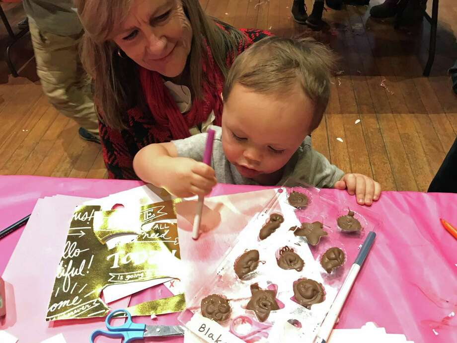Pequot Library volunteer Lisa Lane helps participant Blake Heathcock create Valentine's Day treats at the library's 14th annual Kids Candy Making Workshop on Feb. 11, 2019. Photo: Kendra Wingate / For Hearst Connecticut Medi