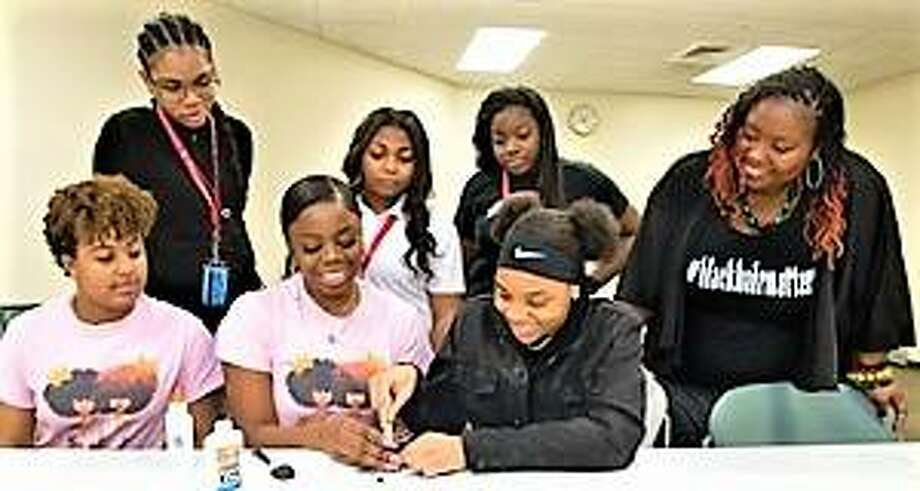 SIUE East St. Louis Charter High School students and SIUE MyCURLFRIENDS members work on making a hair mask. In the front row (L-R) Persephone Cole, a senior majoring in civil engineering; Jayla Howard, a junior majoring in exercise science; and Jaslene Young, CHS junior. Watching from the back row (L-R) Kayla Dawson, CHS senior; Aleesia Glass, CHS junior; Kaneika Bullard, CHS senior; and SIUE's Makesha Harris Lee, EdD, assistant director for Pre-Collegiate Programs. Photo: For The Telegraph
