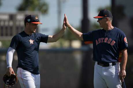 Houston Astros third baseman Alex Bregman, left, and  manager AJ Hinch high-five each other after defense drills at Fitteam Ballpark of The Palm Beaches on Day 9 of spring training on Friday, Feb. 22, 2019, in West Palm Beach.