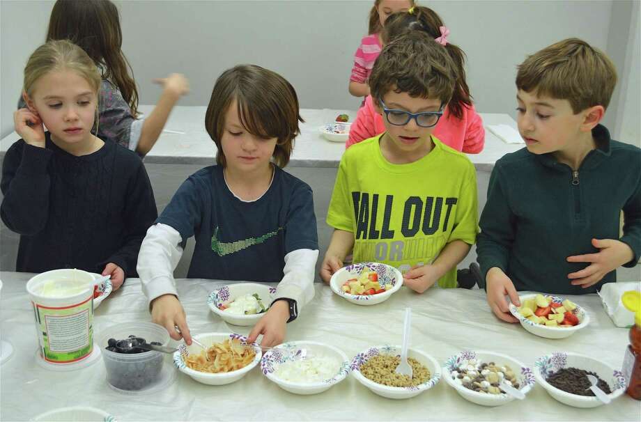 """From left, Carwyn Pullen, 7, Jack Pestka, 6, Lucas Kuen, 6, and Leo Kurtz, 6, all of Fairfield, look over the topping options at the """"Good Reads, Good Eats"""" program at the Fairfield Woods Branch Library on Thursday, Feb. 21, 2019, in Fairfield, Conn. Photo: Jarret Liotta / For Hearst Connecticut Media / Fairfield Citizen News Freelance"""
