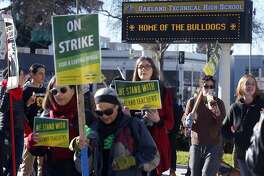 Teachers walk on a picket line in front of Oakland Technical High School on the first day of the teachers strike in Oakland, Calif. on Thursday, Feb. 21, 2019.