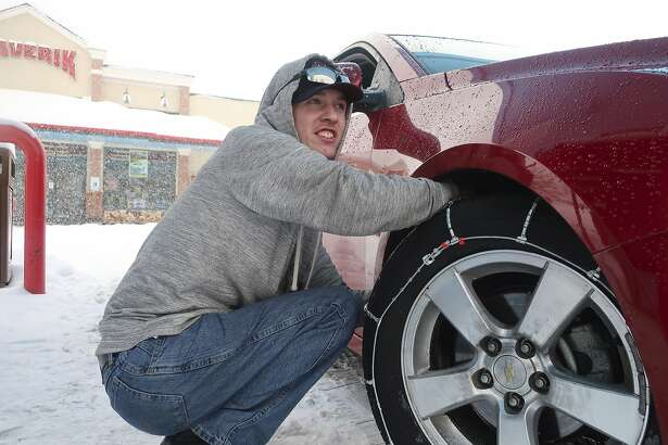 Taylor Killian puts snow chains on the vehicle he's driving during a trip to Flagstaff, Arizona, on Thursday, Feb. 21, 2019. Schools across northern Arizona canceled classes and some government offices decided to close amid a winter storm that's expected to dump heavy snow in the region. (AP Photo/Felicia Fonseca)
