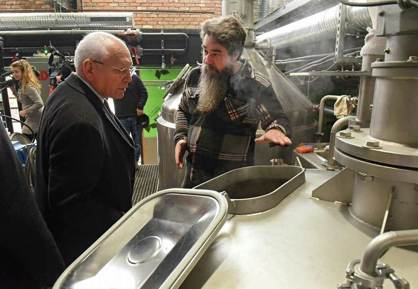 Master Brewer Rich Michaels, right, explains the beer making process to Congressman Paul Tonko as he takes a tour of the Frog Alley Brewing at the Mill Artisan District construction project on Friday, Feb. 22, 2019 in Schenectady, N.Y. (Lori Van Buren/Times Union)