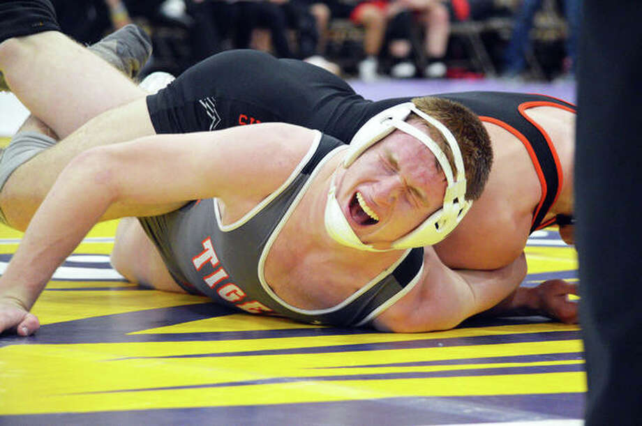 Edwardsville's Drew Gvillo (bottom) grimmaces as he wrestles in the 152-pound match during the Class 3A Taylorville Dual Team Sectional on Tuesday. Photo: Matt Kamp | For The Telegraph