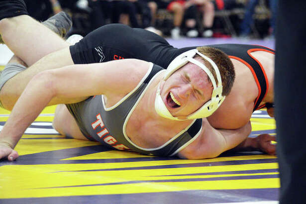 Edwardsville's Drew Gvillo (bottom) grimmaces as he wrestles in the 152-pound match during the Class 3A Taylorville Dual Team Sectional on Tuesday.