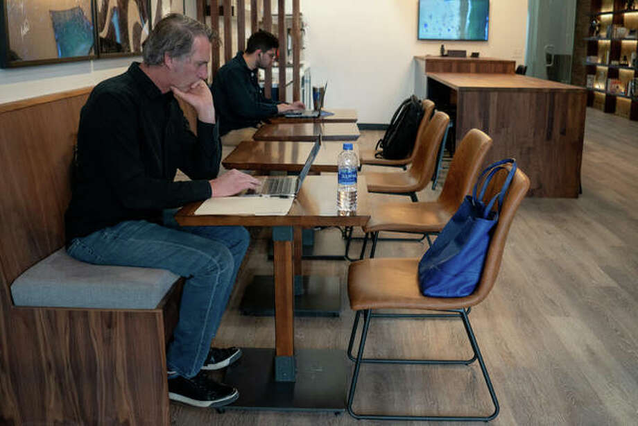 Owner of Edwardsville's The Lodge Jay Beard, left, and member Cody Savoie work at the coffee-style seating in the general room for members this week. Photo: Bre Booker | The Intelligencer