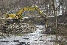 Excavator operator Jarrod Martellacci, works on removing the Old Papermill Dam on the East Aspetuck River. The dam belongs to the Ousatonic Fish & Game Protection Association and its removal is being overseen by the Nature Conservancy. Friday, February 22, 2019, in New Milford, Conn.