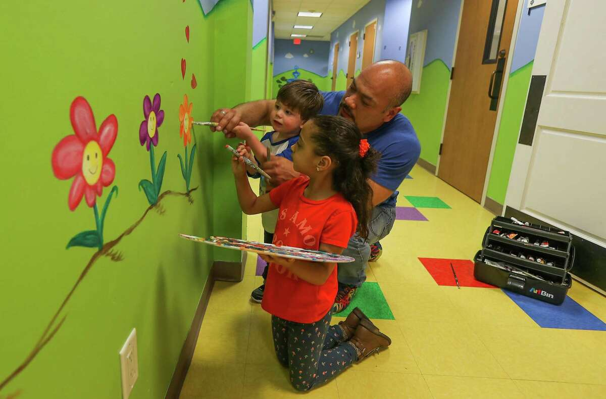 """Oscar Spivey and his daughter Sophia, 6, work on a mural at Bering United Methodist Church. Oscar and his husband Mitch drive 41 miles each way from their home in Fulshear to worship at Bering, which Mitch calls """"the most welcoming place I've ever experienced."""""""