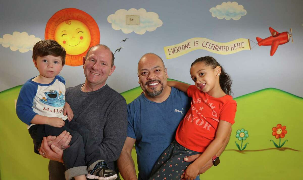 """Mitch and Oscar Spivey and their children (Sophia, 6, and Matthew, 2) belong to Bering United Methodist Church, which is pushing for its denomination to recognize LGBT relationships. """"Bering has been only place where I can worship God, be who I am, and be accepted,"""" says Oscar, who painted this mural in a Bering hallway."""