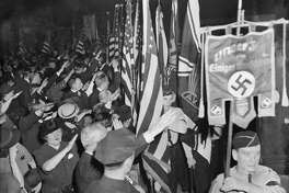"""Snapping into the regulation Nazi salute, Bund members hail the swastika banner as it is paraded in Madison Square Garden during opening ceremonies of the German American Bund's """"Pro-American Celebration of George Washington's Birthday."""" A riot squad of 1,700 policemen, largest in police history, was concentrated in and around Madison Square Garden as an estimated 80,000 anti-Nazi demonstrators gathered in threatening mobs about the Garden."""