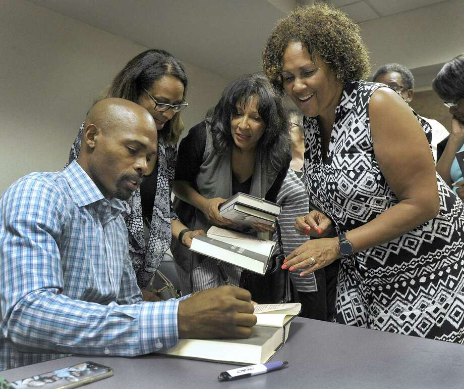 "Physician and best-selling author Ian Smith, a Danbury native, signs his latest book, ""The Ancient Nine,"" at a discussion in September at Danbury Library for childhood friends, from left Tracey Gonzalez, Cynthia Houston and Jackie Elam. Ian as well as his twin brother, Dana, were recipients of Hord Foundation scholarships in their youth and 10 percent of the proceeds from books sales that evening went to the foundation. Photo: Carol Kaliff / Hearst Connecticut Media / The News-Times"