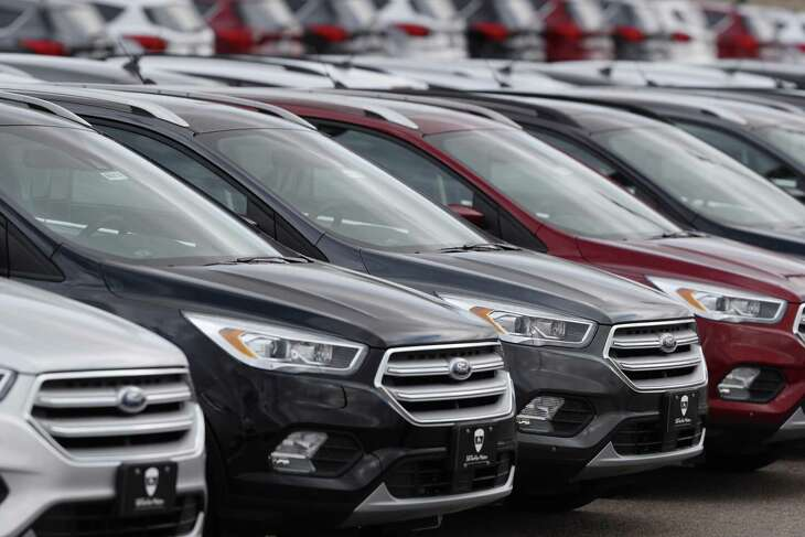FILE-In this Sunday, Feb. 17, 2019, file photograph, unsold 2019 Escape sports-utility vehicles sit in long rows at a Ford dealership in Broomfield, Colo. (AP Photo/David Zalubowski)