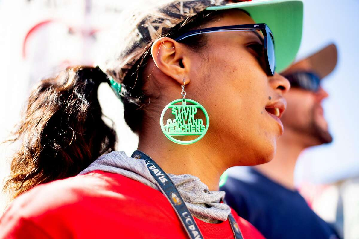 India Leeward, a teacher at Oakland's New Highland Academy, wears protest earrings while rallying in DeFremery Park on Friday, Feb. 22, 2019, in Oakland, Calif. Several hundred people showed up for the protest during day two of the Oakland teacher strike.