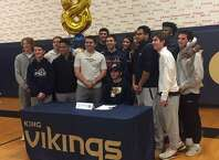 Matt Garavel, seated, celebrates with his King School football teammates Friday after signing his letter of intent to play football at Pace University in the fall.